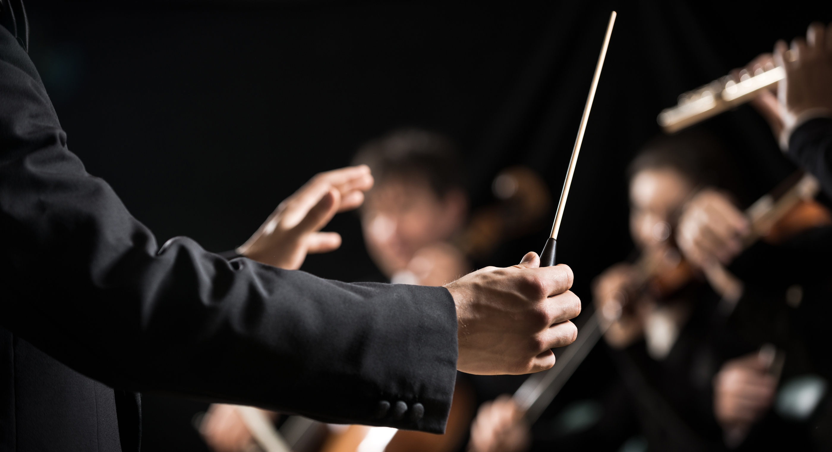 Conductor directing symphony orchestra with performers on background hands close-up.